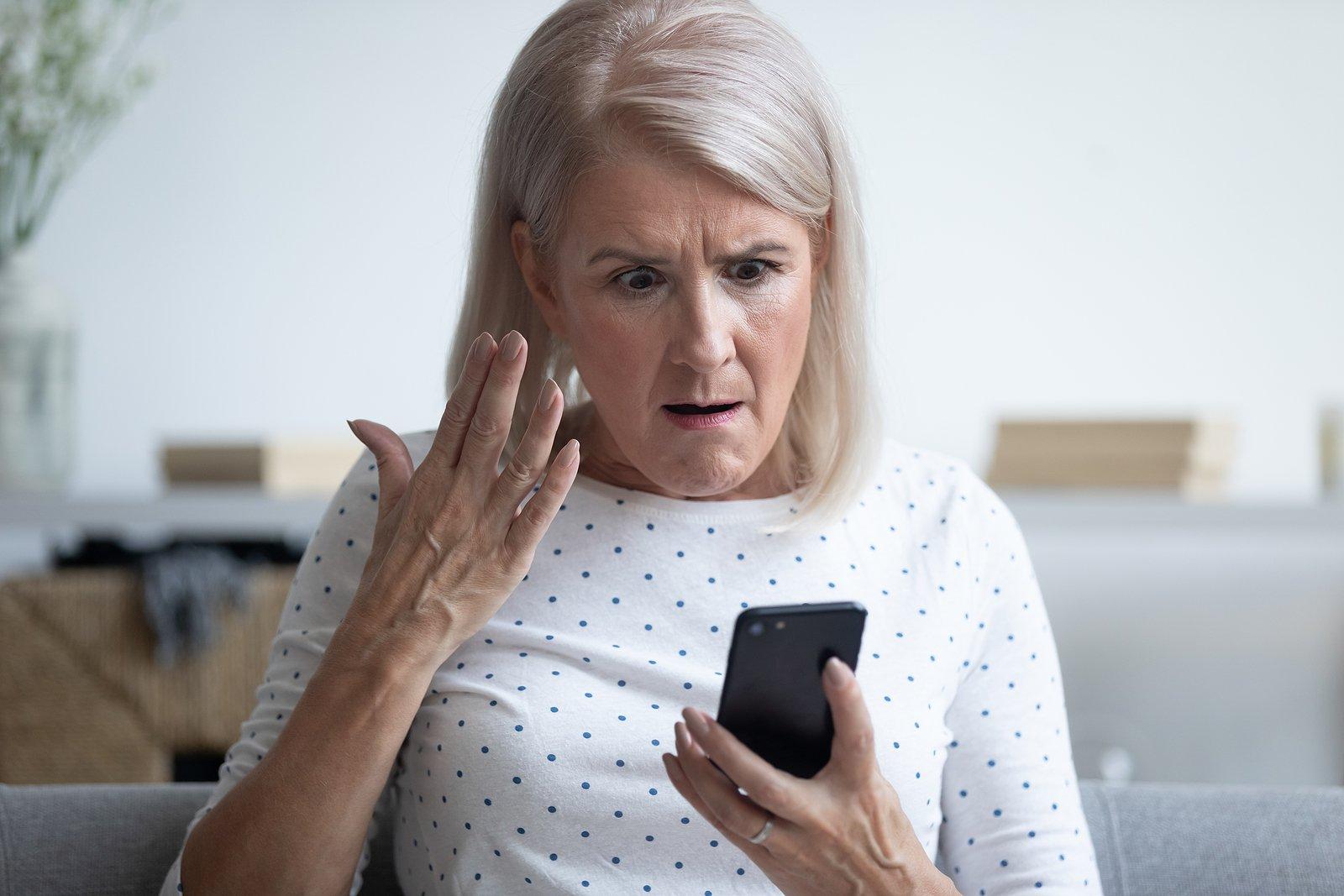 bigstock-Mad-Elderly-Woman-Holding-Smar-336837388